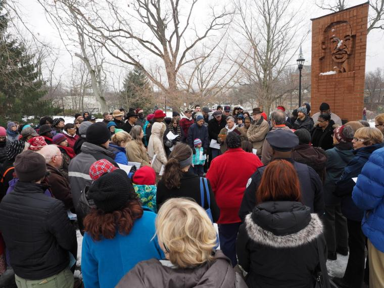 People gathered around a brick structure with a depiction of the face of Martin Luther King Jr.