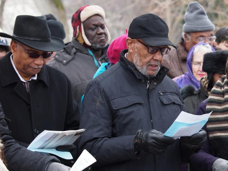 People dressed in winter gear stand in a crowd, reading from pieces of paper