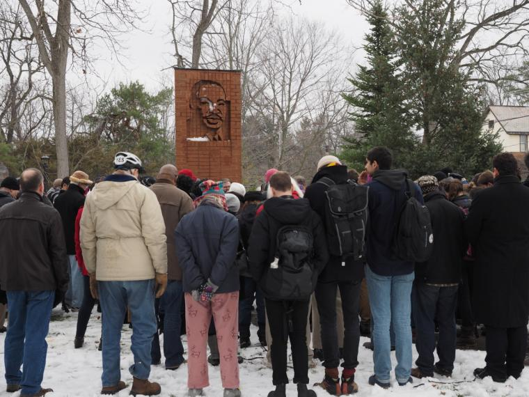People stand in a crowd on the snow-covered ground around a brick structure with a depiction of the face of Martin Luther King Jr.