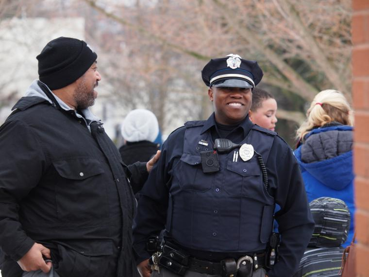 A police officer smiles with another man