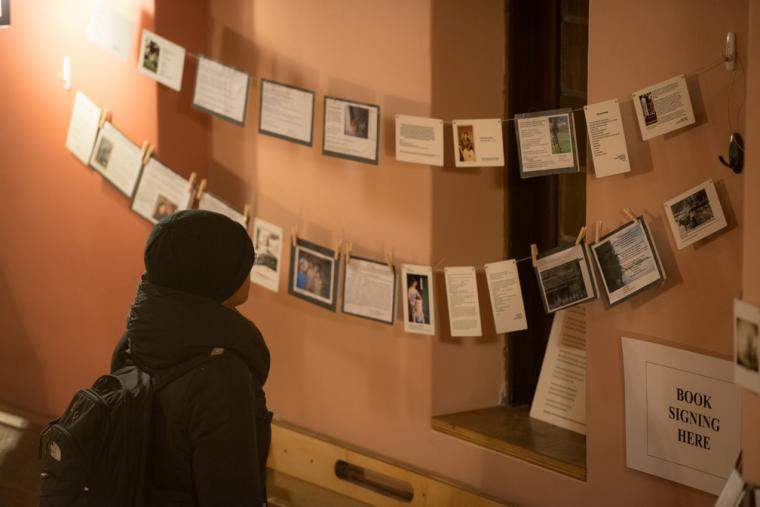 Photograph of someone looking at signs that are hanging.