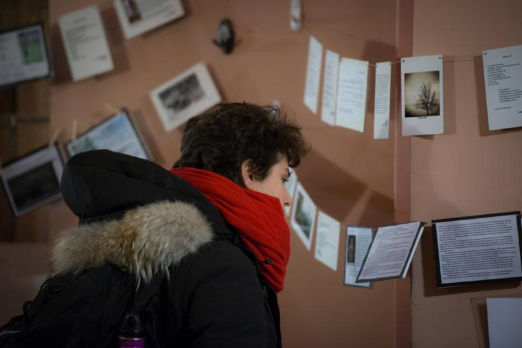 Photograph of someone viewing the signs and images that are hanging.