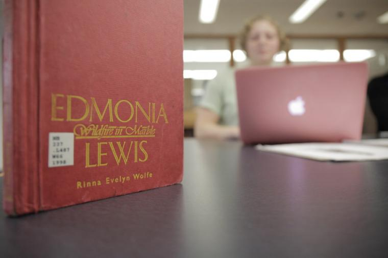 A photo of a red book by Edmonia Lewis in the foreground, while a student works at their laptop in the background