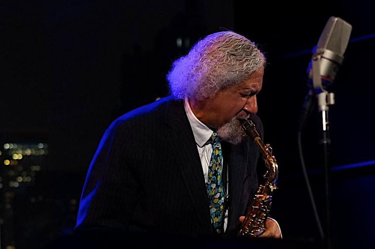 Photograph of a man playing a saxophone.