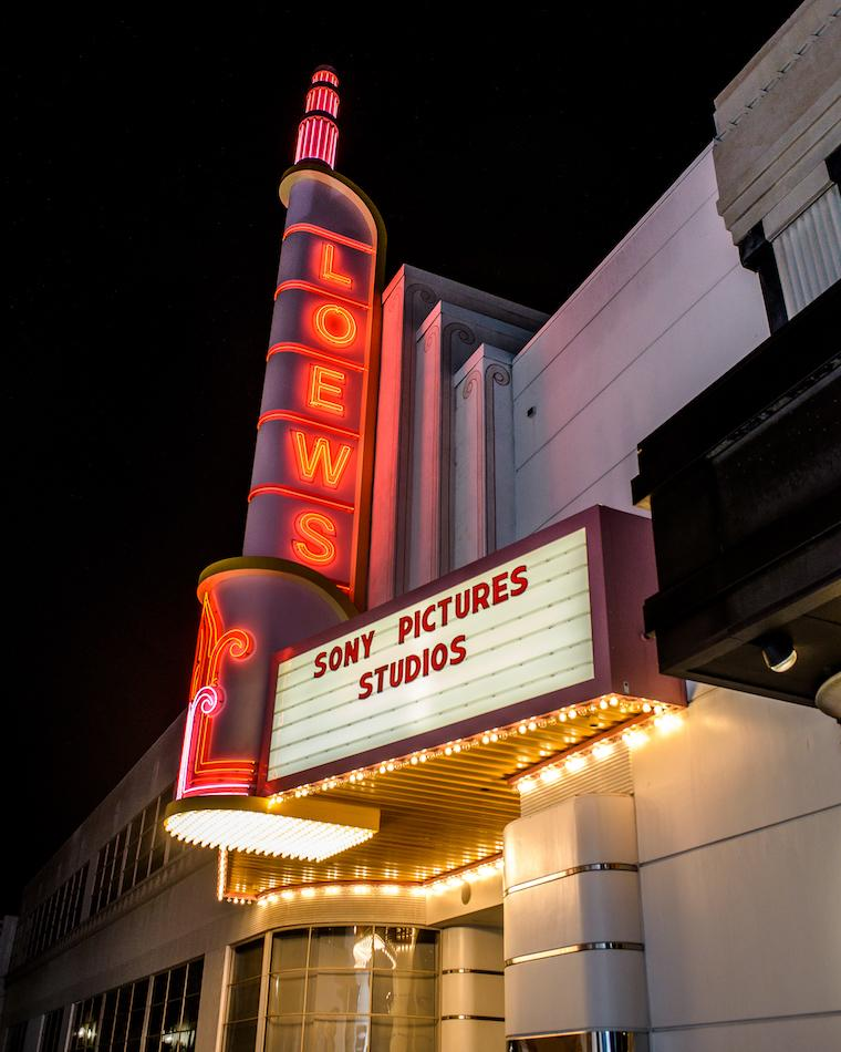 Loews theater sign fully lit at night, with Sony Pictures Studios on the marquee.