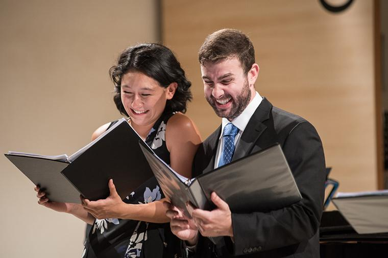 A man and woman share a laugh while looking at open binders