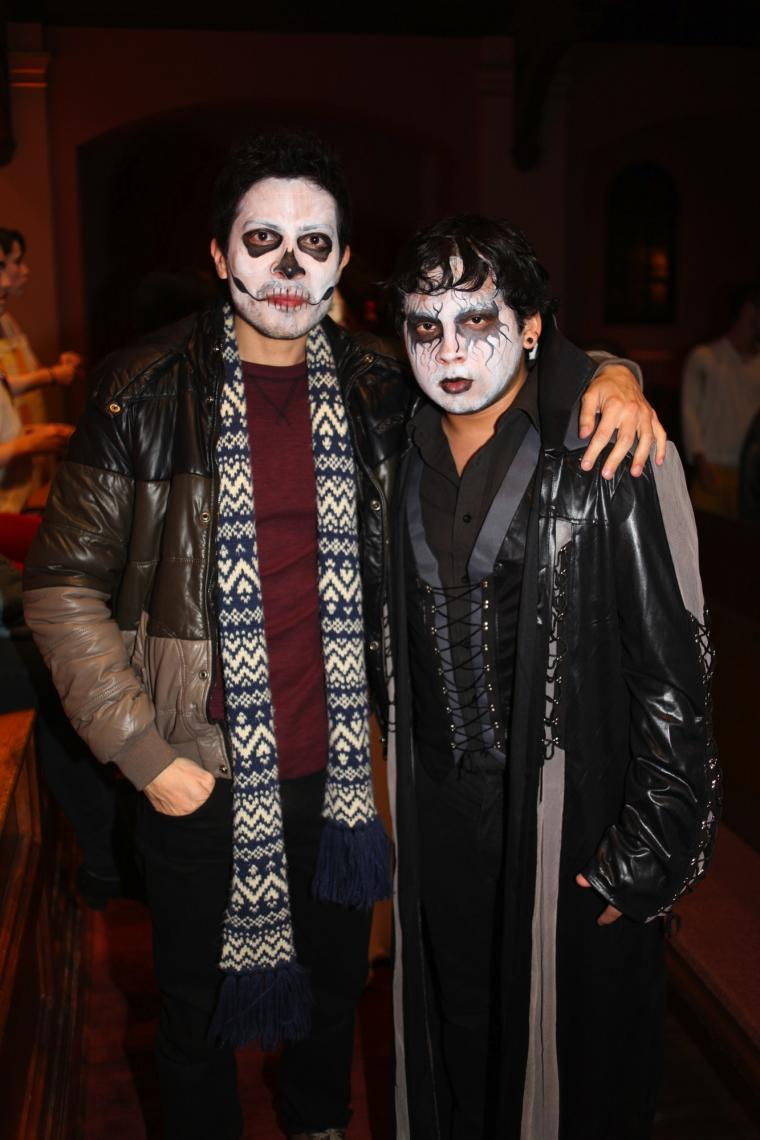Two people in halloween makeup pose for a photo