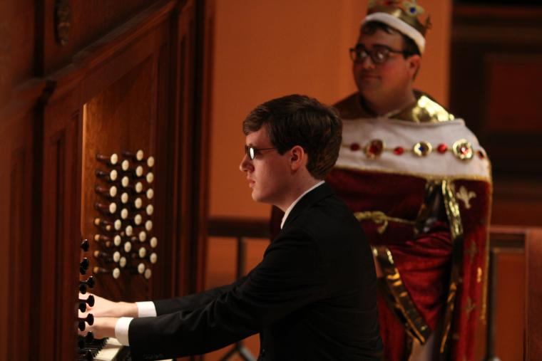 A person in a suit performs at an organ while another, dressed in a royal costume, stands nearby