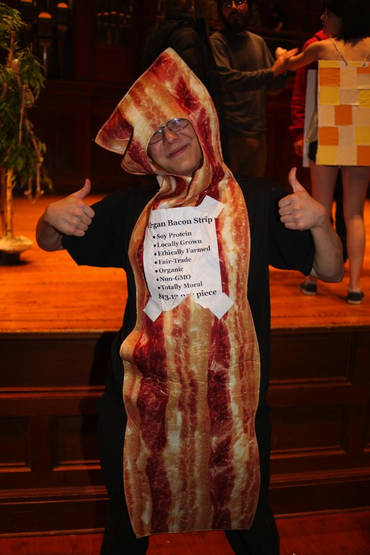 A person in a bacon costume poses for a photo