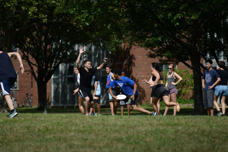 Photograph of people playing frisbee in the yard.