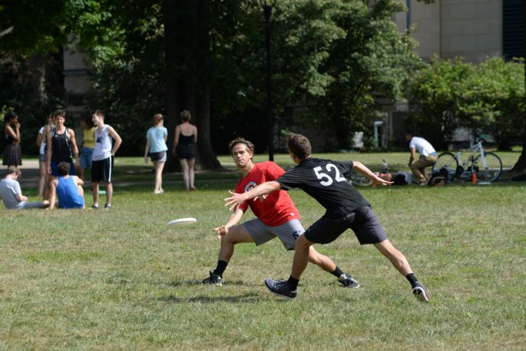 Photograph of two men playing frisbee.
