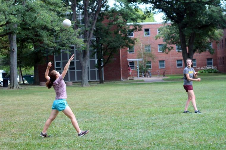Photograph of two women playing volleyball.