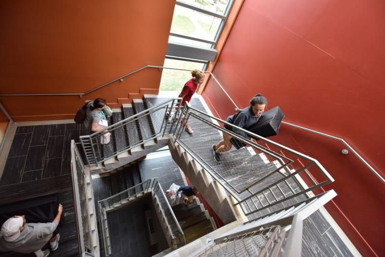 Photograph of people walking up a stairwell.