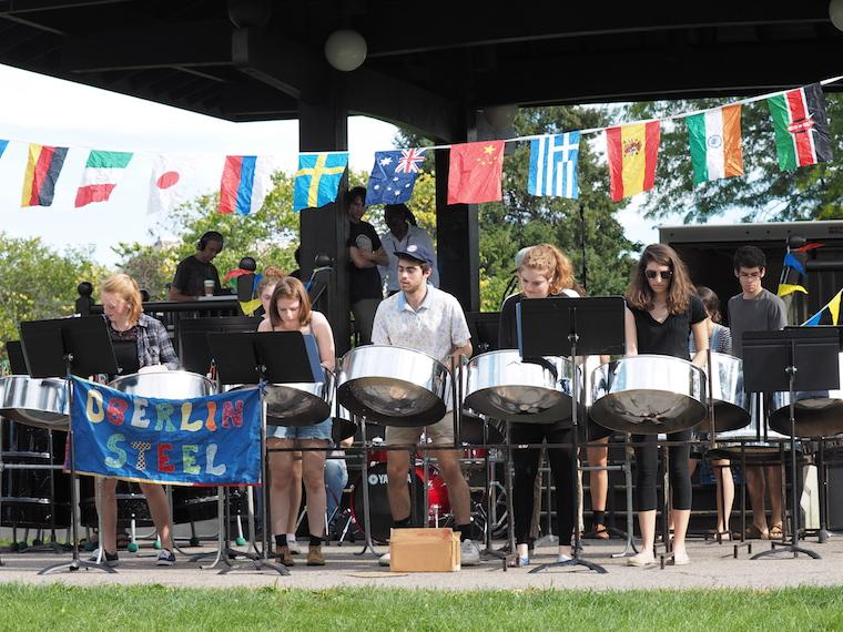 students lined in a row playing steel drums