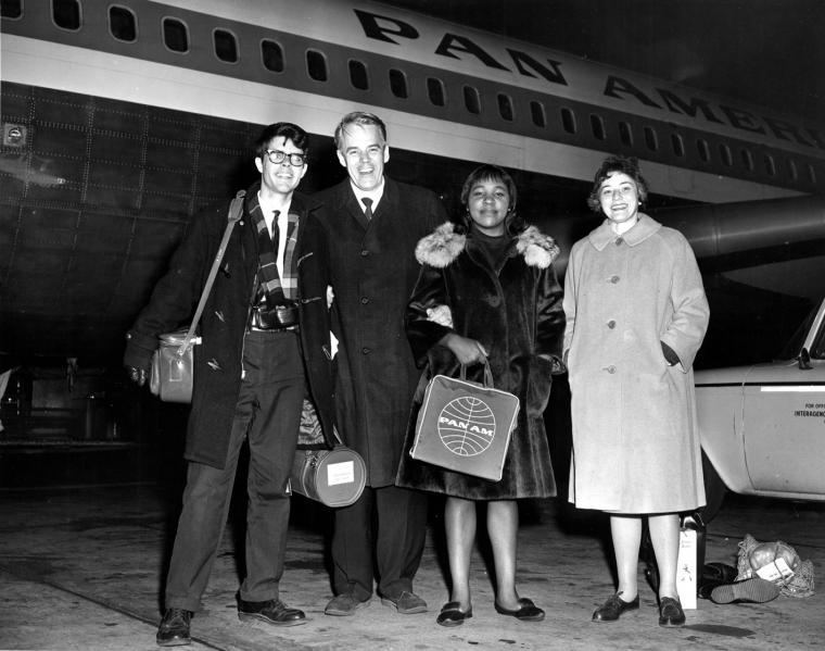 Black and white photo of four people posing in front of a Pan Am aircraft