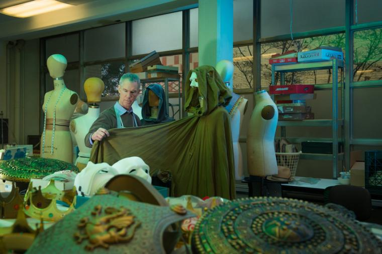 A man surveys part of a costume placed on a mannequin in a room filled with assorted costume materials
