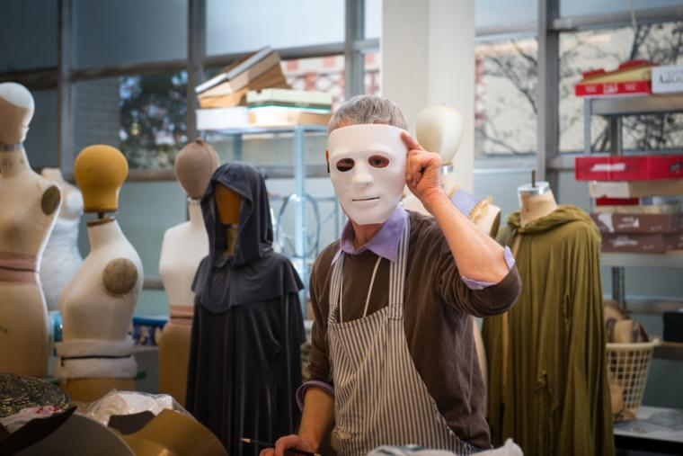A man wears a mask while surrounded by costume mannequins