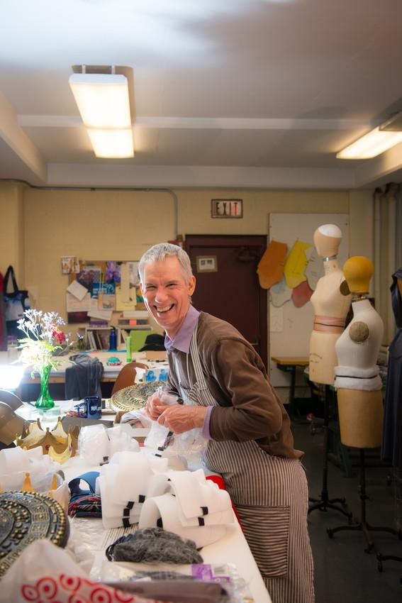 A man smiles in a room filled with costume materials