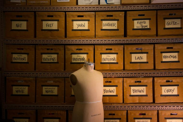 A mannequin placed in front of rows of boxes with labels identifying different craft materials