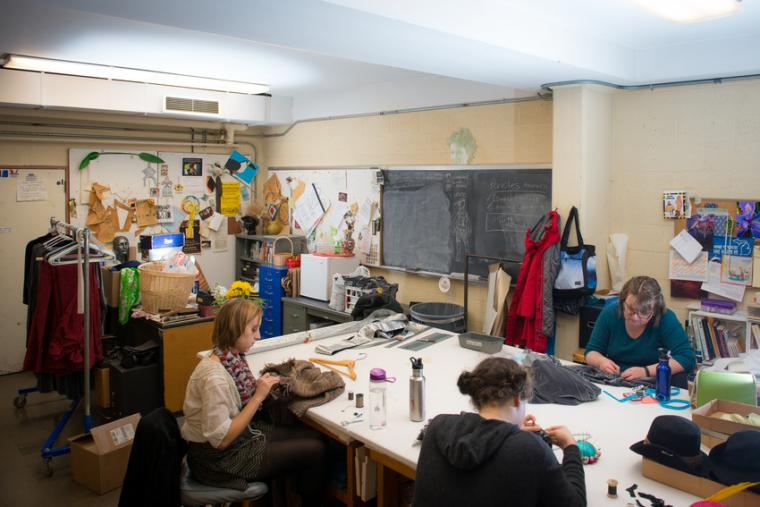 Three people sit around a table working on costume fabric