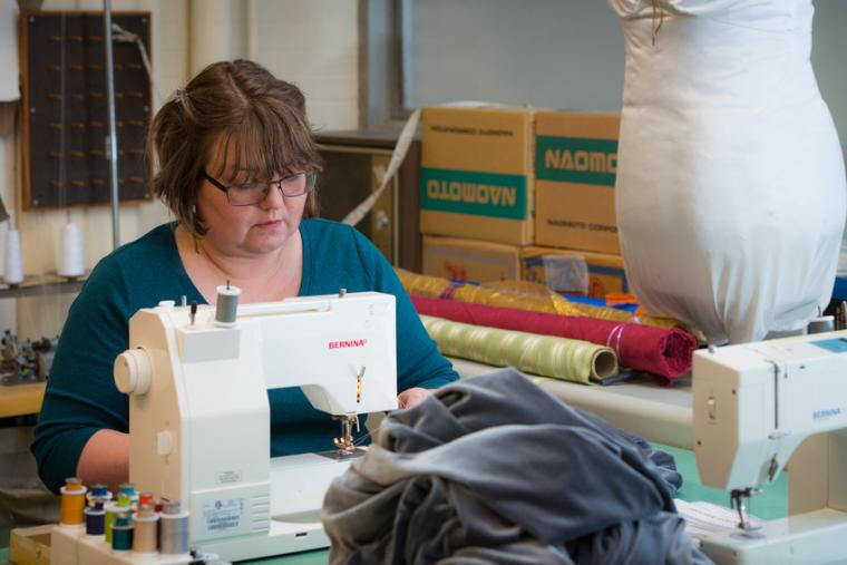 A woman works at a sewing machine