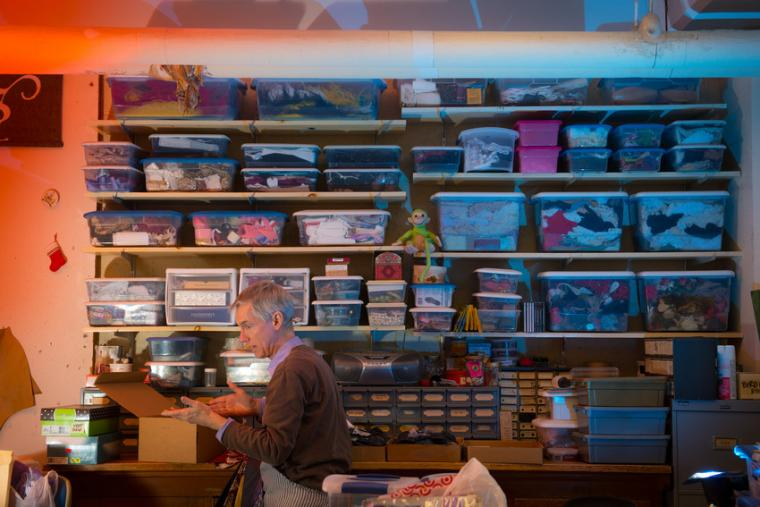 A man looks in a box in front of shelves filled with boxes of costume material