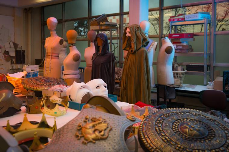 A array of costuming materials laid out on a table, surrounded by mannequins