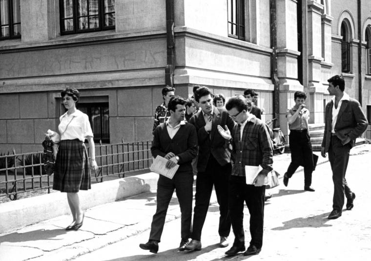 Black and white photo of people walking down a street