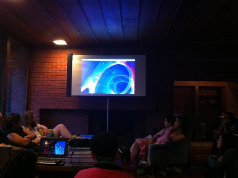 A group of people seated around a projection on a projection screen