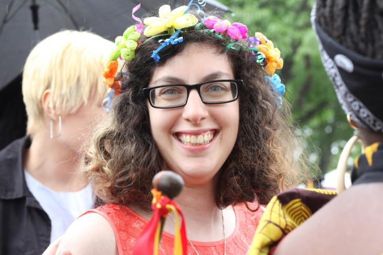 A person wearing a floral headdress smiles