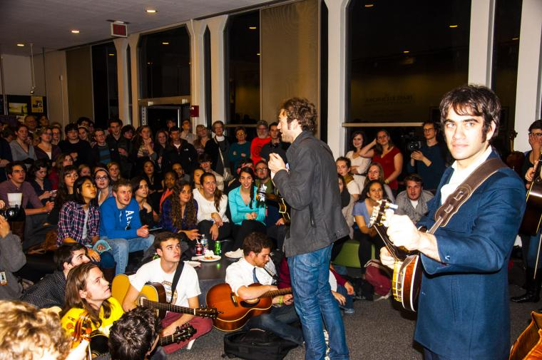 A couple musicians address a crowded room