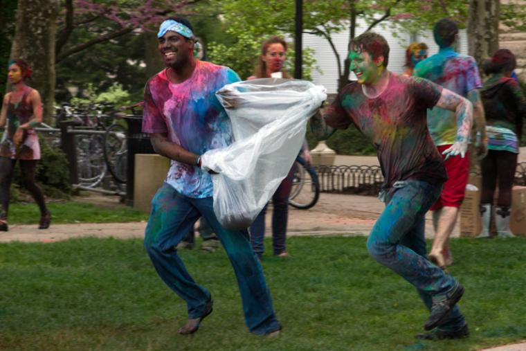 Two people covered in colorful powder run across a field carrying a plastic bag between them