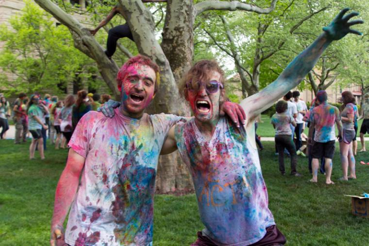 Two people covered in colorful powder pose for a photo