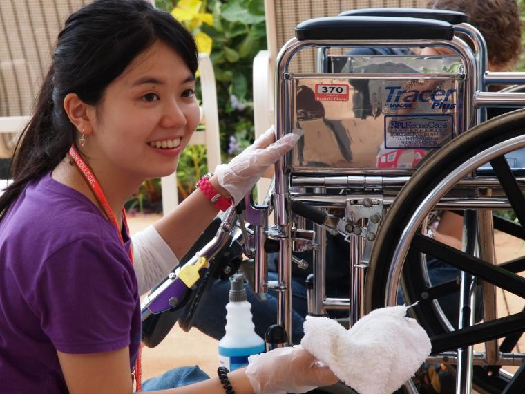 A woman smiles during a pause in cleaning wheelchairs