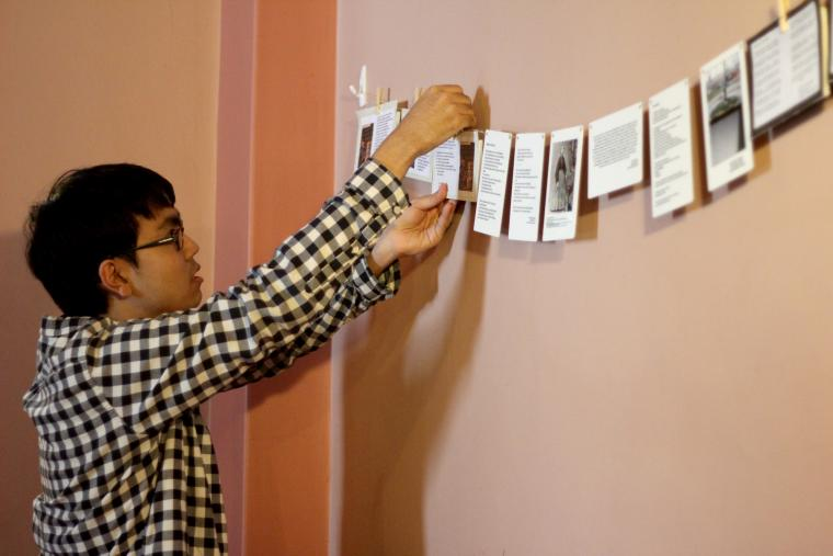 Photograph of a man hanging signs.