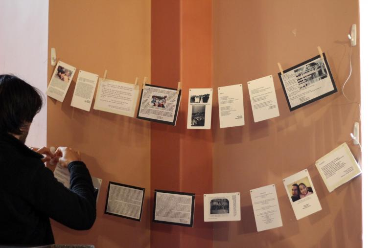 Photograph of someone arranging signs that are hanging