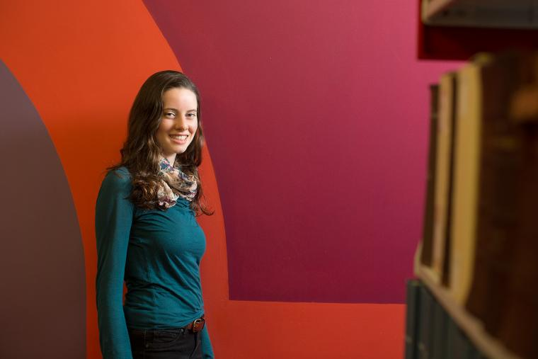 Photo of a woman standing in front of a colorful wall