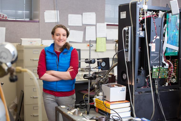 Photo of a person standing amidst lab equipment