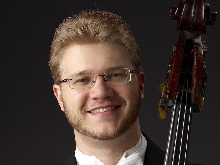 double bass teacher Derek Zadinsky in tux with top of bass visible.