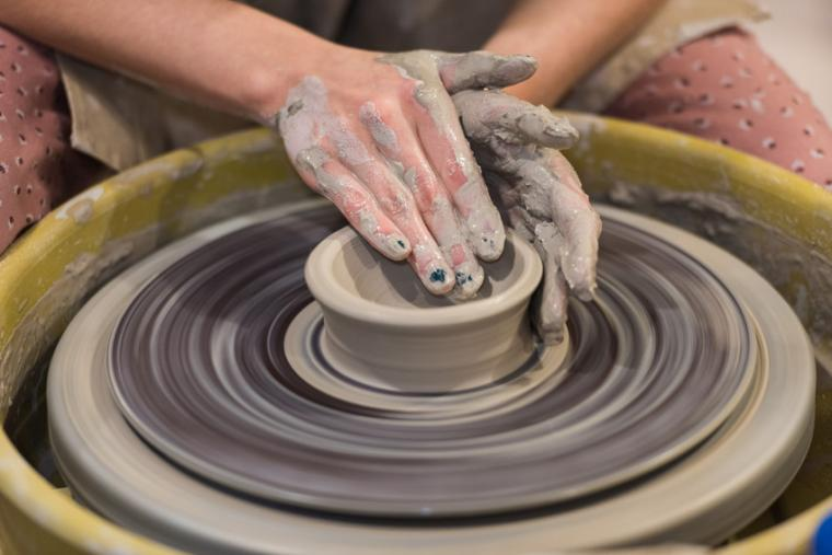 A person shapes a piece of clay on a potter's wheel
