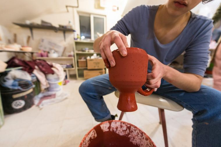 A person holds a piece of pottery coated in red glaze