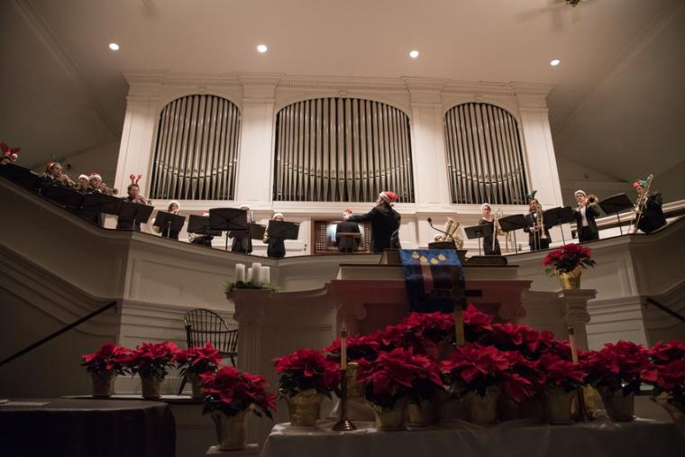 A brass band dressed in santa hats performs in a church decorated with poinsettias