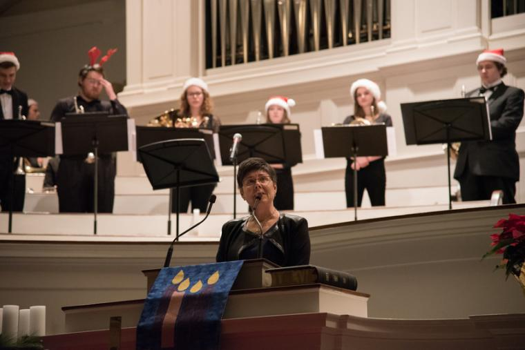 A woman speaks at a podium while a brass band waits in the background