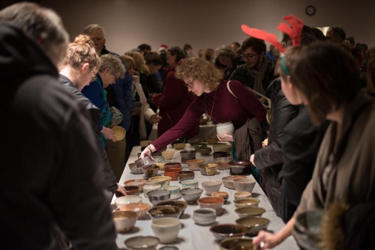 Many people mingle around a table filled with pottery