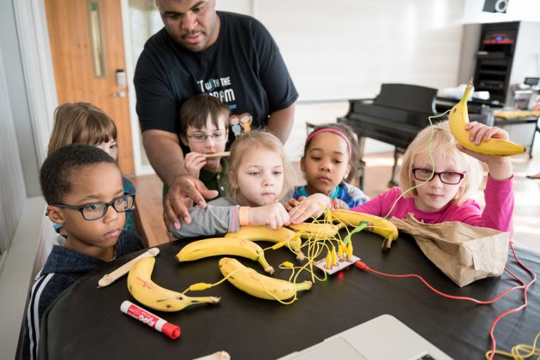 Jason Williams '05 helps a group of children plug wires into bananas