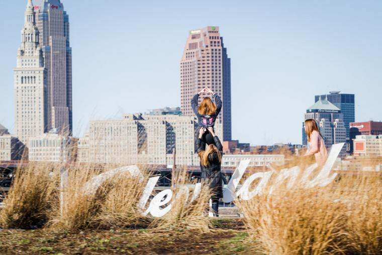 "Photograph of a city backdrop, a sign that says, ""Cleveland,"" and three women posing by the sign."