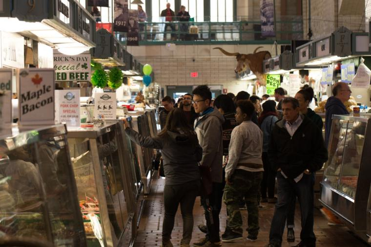 Photograph of men and women in the West Side Market located in Cleveland, Ohio.
