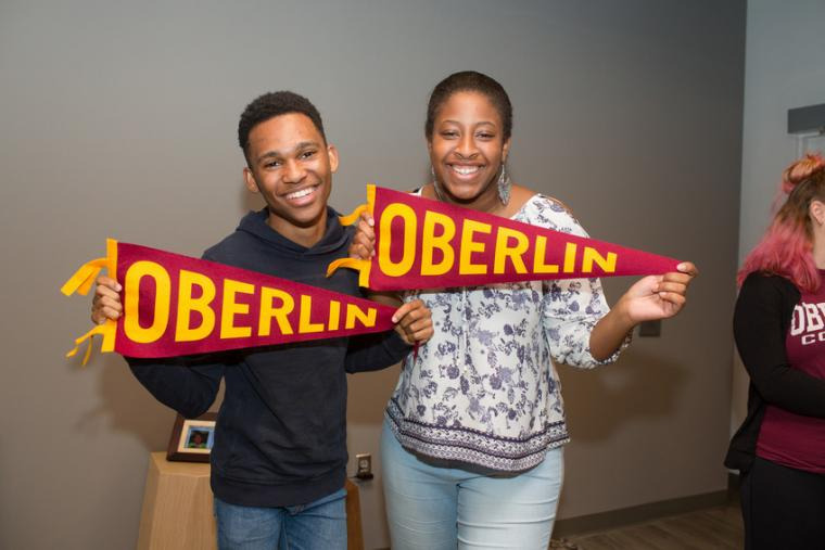 Photo of two high school students holding Oberlin pennants