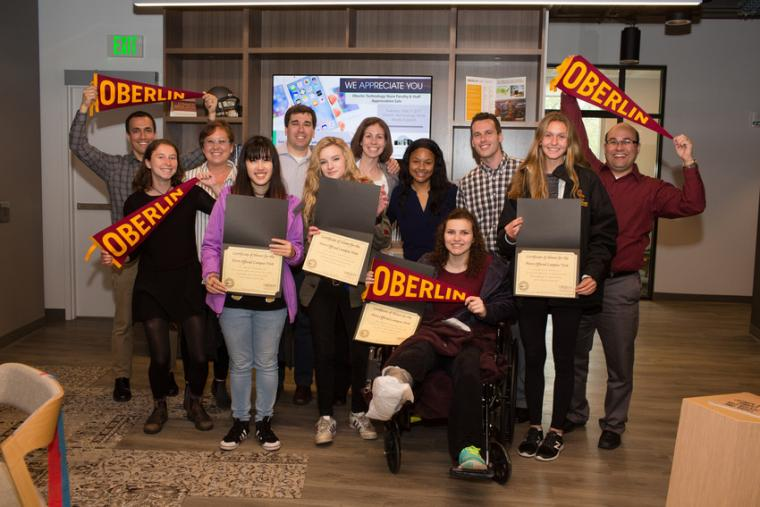 Photo of group of visiting families holding Oberlin pennants and certificates