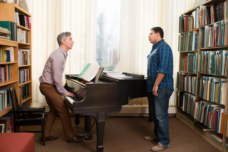A professor stands and plays a piano while a student sings in a brightly lit room